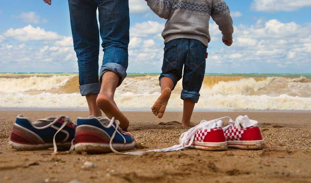 PIeds d'enfants et d'un père sur la plage en train de courir
